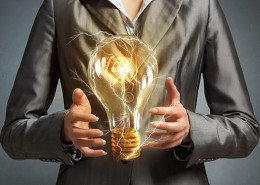 Close up of businesswoman holding glass glowing light bulb in hands